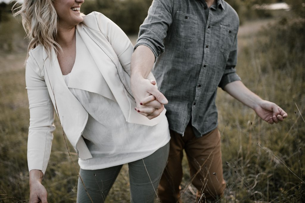 Nebraska Engagement Photos holding hands and bumping hips